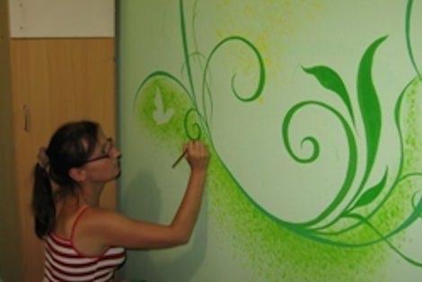 Девушка рисует на стене